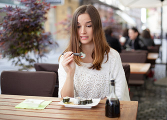 Young woman hesitant about eating sushi