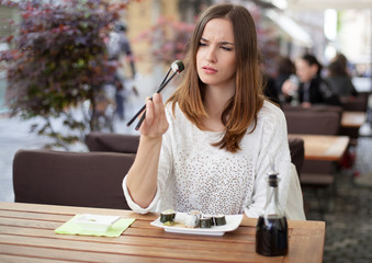 Young woman unsure about eating sushi