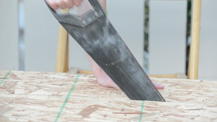 Side view of man sawing wood plank, blows dust