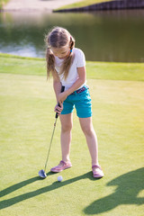 Cute little girl playing golf on a field