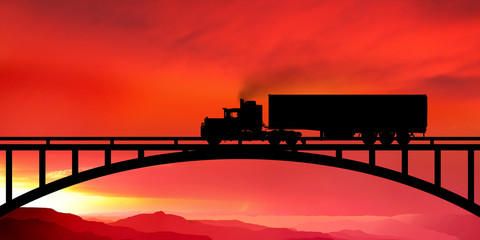 Silhouette of a truck on a bridge at sunset