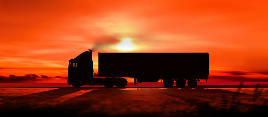 Silhouette of a truck on a highway at sunset