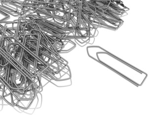 messy heap of silver paper clips on a white background