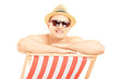 Smiling guy wearing hat and sunglasses, posing on a beach chair