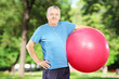 Smiling mature man holding a pilates ball in park