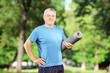 Smiling mature man holding an exercising mat in park