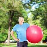 Mature man holding a pilates ball in park