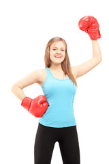 Happy female athlete wearing boxing gloves and gesturing triumph