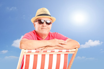Smiling mature man wearing hat and sunglasses, posing on a beach