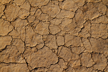 Dry cracked earth and dirt with grains of sand