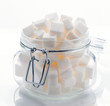 glass jar full of white sugar cubes on white base