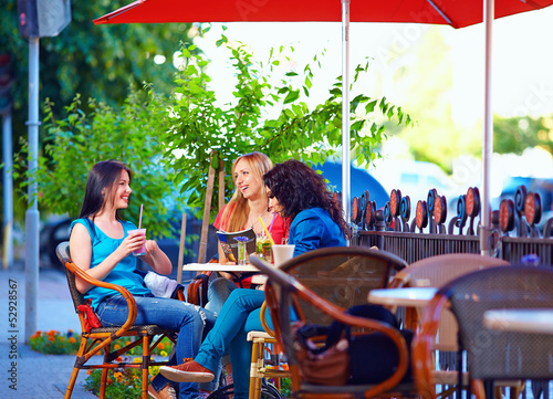 beautiful young women sitting on cafe terrace