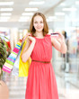 Beautiful young woman with shopping bags and credit card