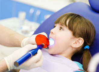 little girl with open mouth receiving dental filling drying proc
