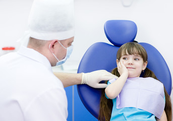 little girl holding her cheek with a toothache at dentist's offi