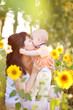 Happy family in spring field of beautiful sunflowers