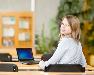 girl using computer in a library. looking at camera