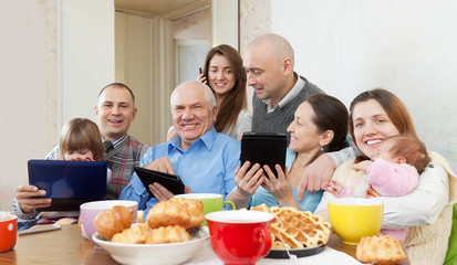Happy family or friends with electronic devices