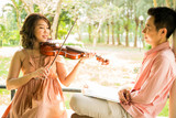 woman playing violin with her boyfriend