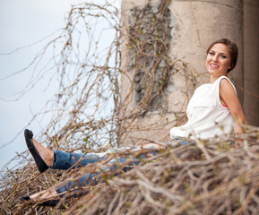 Beautiful young woman sitting in a vine