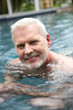 Grey-haired man swimming in the pool