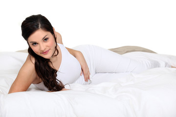 Cute brown-haired woman lying on a bed
