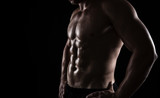 Close up of perfect male body isolated on black background