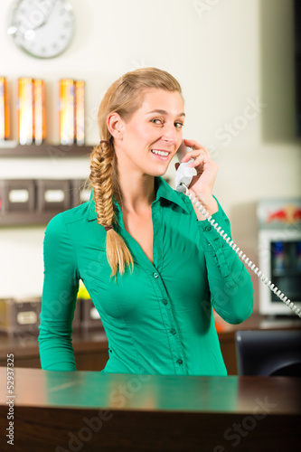 Woman taking a call at gym reception