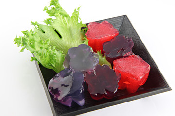 Red jelly and purple jelly in dish.