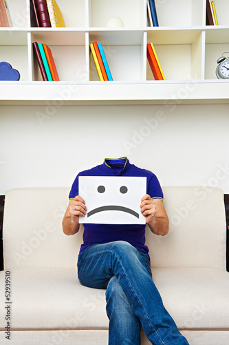 faceless man sitting on sofa