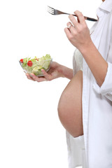 Cropped picture of a pregnant woman eating a salad.
