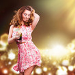lächelnde junge Frau im Sommerkleid und mit Cocktail