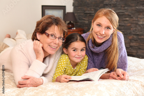 Grandmother, mother, and daughter lying on a bed