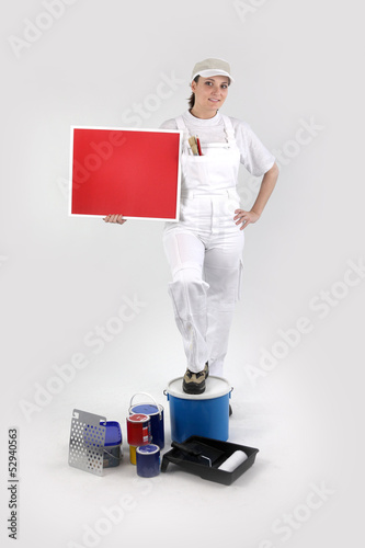 Female decorator stood with red poster