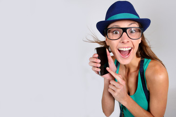 Funny girl with hat and eyeglasses showing smartphone
