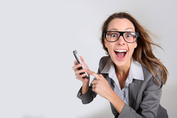 Business girl with funny look showing smartphone