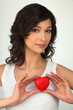 Young brown-haired woman with red heart in hands