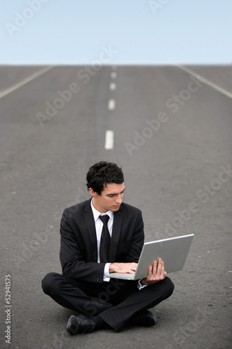Businessman sat on road