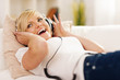 Happy woman listening to music on sofa