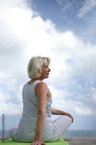 Senior woman doing yoga outdoors