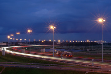 Electric lighting on night the highway. Lighting masts on night