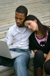 Young couple on some steps with a laptop
