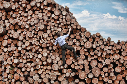 Challenge- businessman climbing the large pile of logs