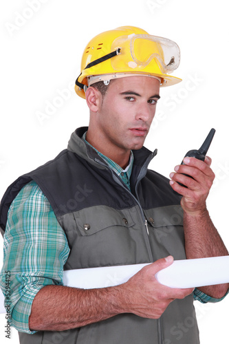 Young foreman using radio to communicate