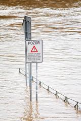Flood in Prague in 2013. Traffic sign on riverside in water.