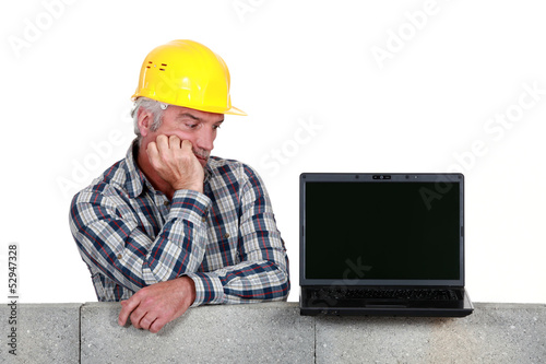Confused middle-aged builder looking at laptop