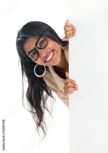 Indian businesswoman peeking from behind blank sign billboard