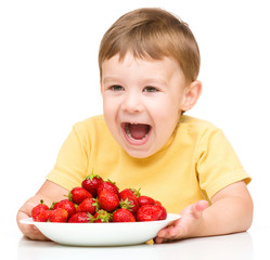 Happy little boy with strawberries