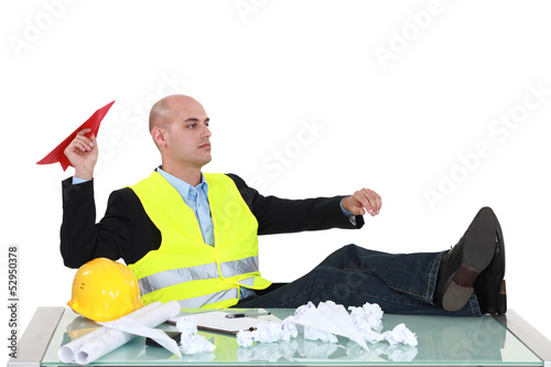 Bored foreman throwing paper airplane