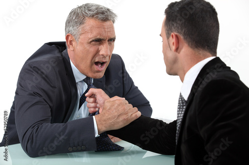 Businessmen fighting at desk